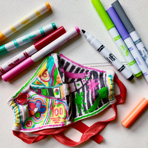 A box of crayola fine line fabric markers with 10 different color markers, a cream face mask and an example of a design it yourself face mask with a kid's drawing.
