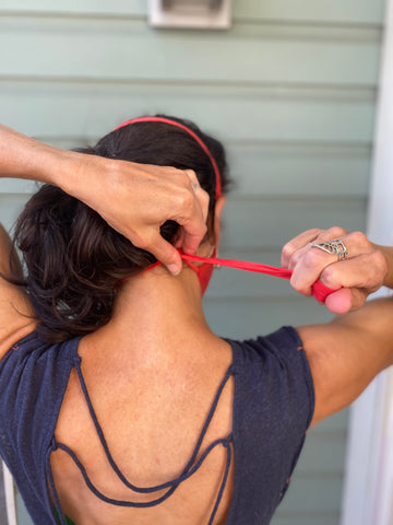 Woman adjusts the elastic head strap of her face mask