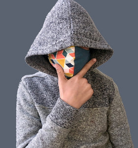 Boy in hoodie wearing geogami geometric and blue design organic cotton face mask.