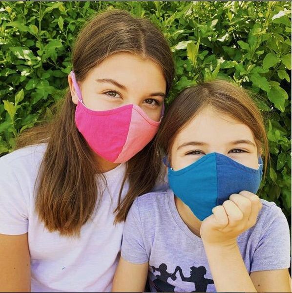 Sisters Wear BringIt! Masks. One Girl Wears Two-Tone Pink. The other girls wears two-tone blue.