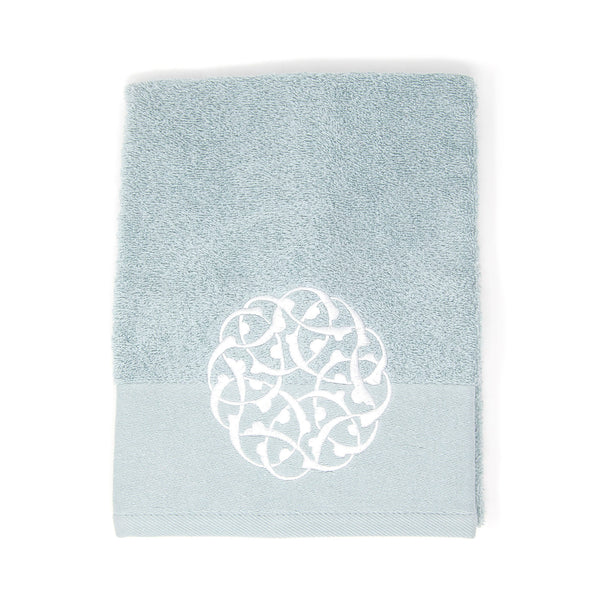 Pale bluish-grey towel with a decorative embroidered white circle in the middle