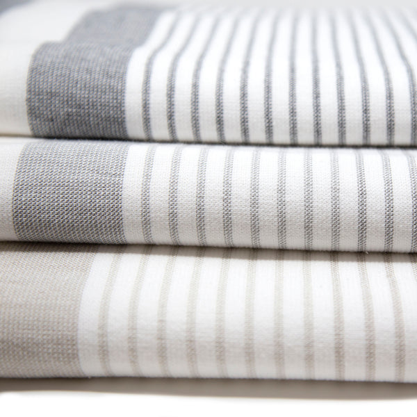 Three large square white towels with a section of thin stripes and two thick stripes in varying colors