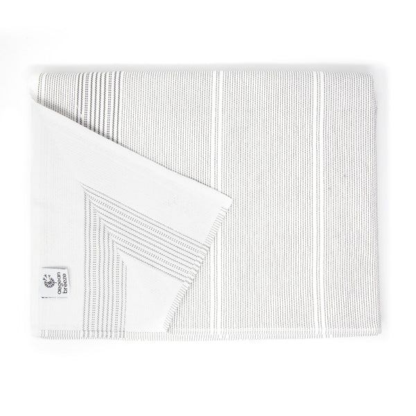 White bath towel with thin grey stripes with a folded corner. Square Aegean Breeze tag attached to the hem.