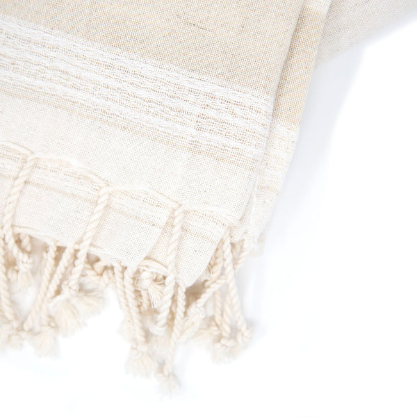 Detailed close-up of off-white towel with beige stripes and corded tassels