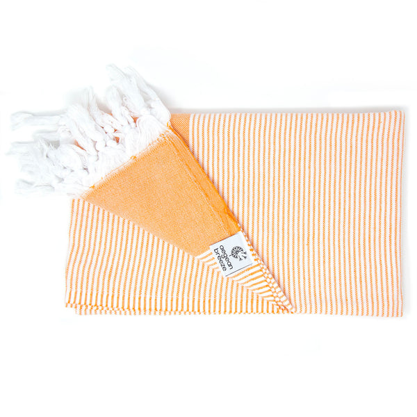 Orange towel with white stripes and tassels. Corner folded. Square Aegean Breeze tag attached to hem