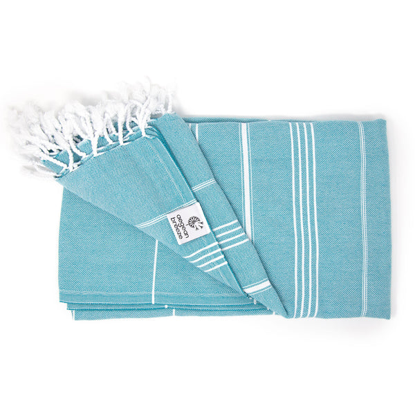 Teal beach towel with thin white stripes and corded tassels. Square Aegean Breeze tag on hem
