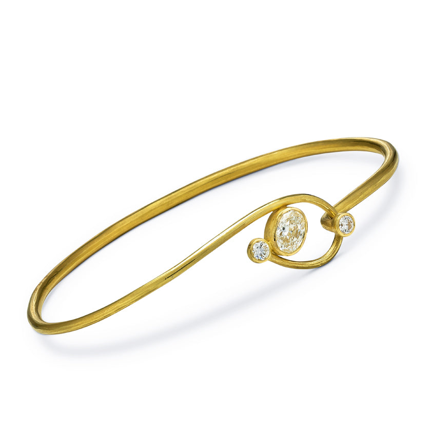 Lasso cuff in 18K gold with a center oval diamond and 2 round diamonds
