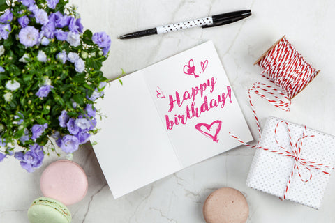 Happy birthday written in a notebook with a present and flowers