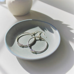 Sterling Silver Orbit Hoops in green dish