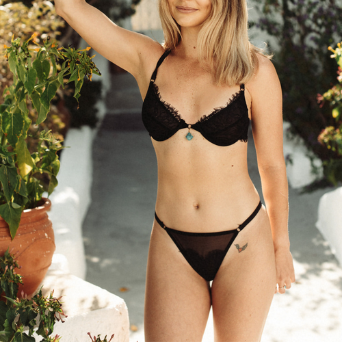 woman standing with a plant pot and is posing for the black bra and underwear with mesh on it