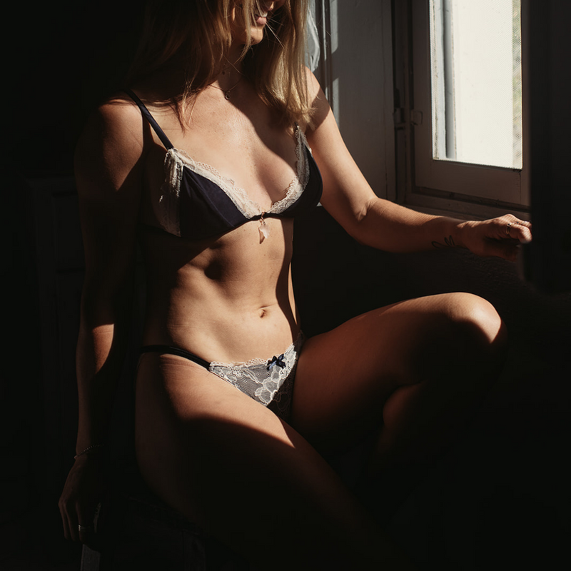 woman sitting near window wearing navy blue and ivory undies and bra