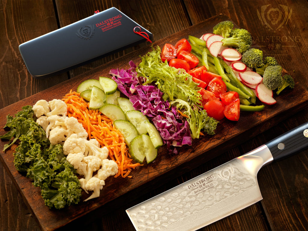 Different vegetables against a wooden surface beside a nakiri knife