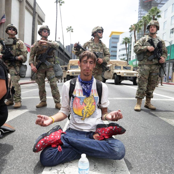 Man meditates in front of Armed Military