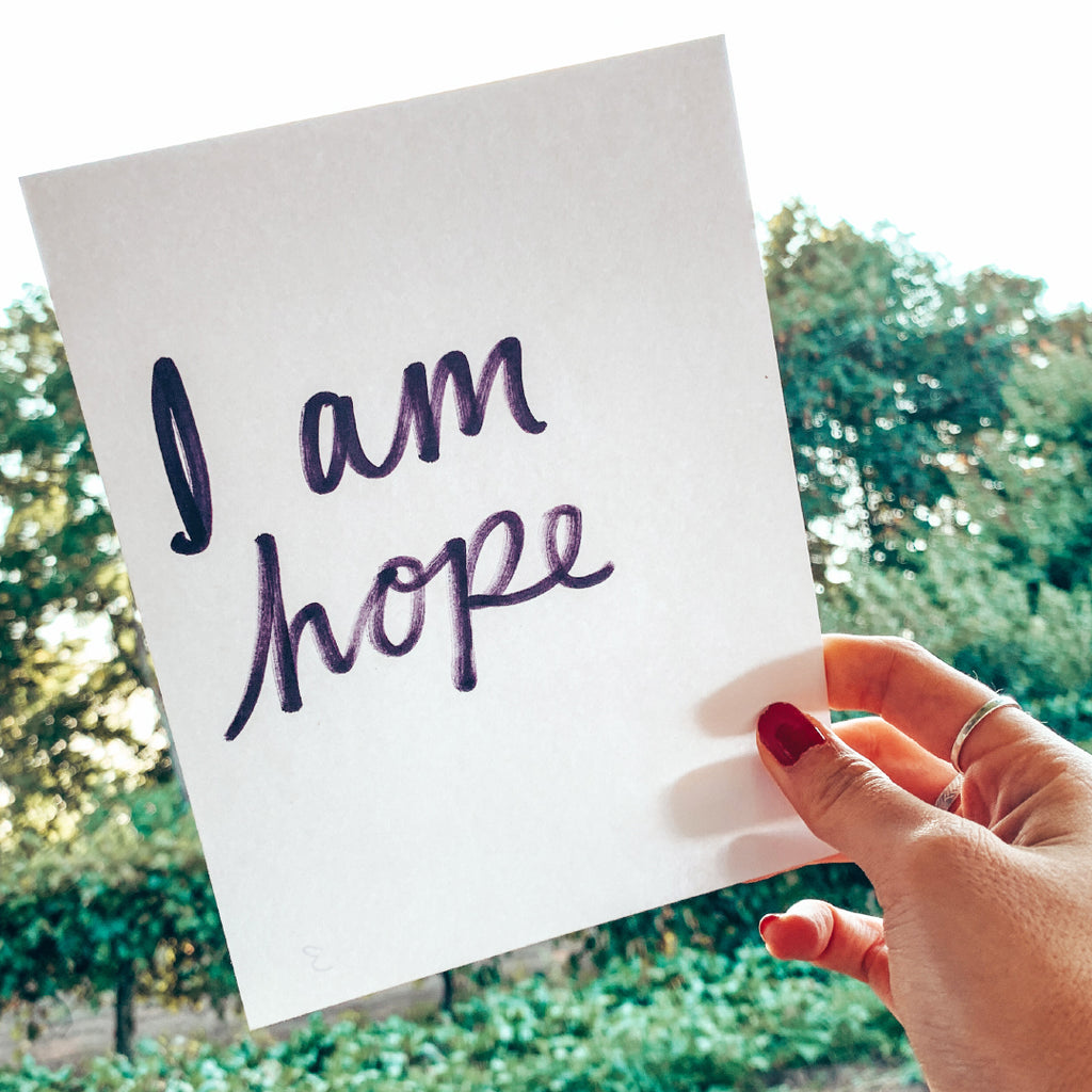 "hand holding card that reads, ""I am hope"""