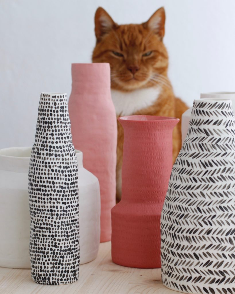 A selection of vases and ginger cat