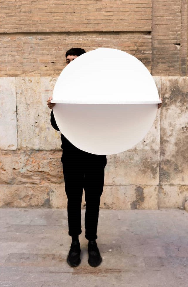 Person holding a big circle mirror