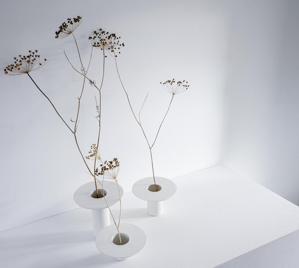 Three white vases with dried flowers