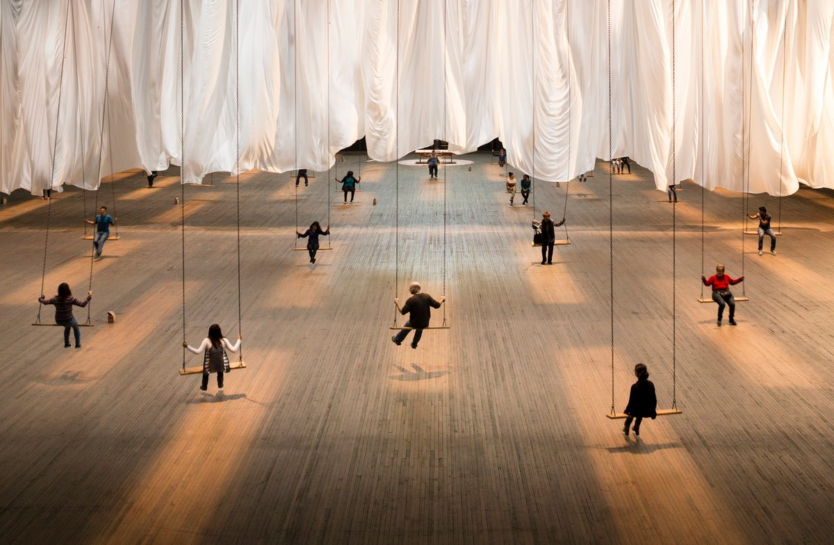 People sitting on swings under white curtains
