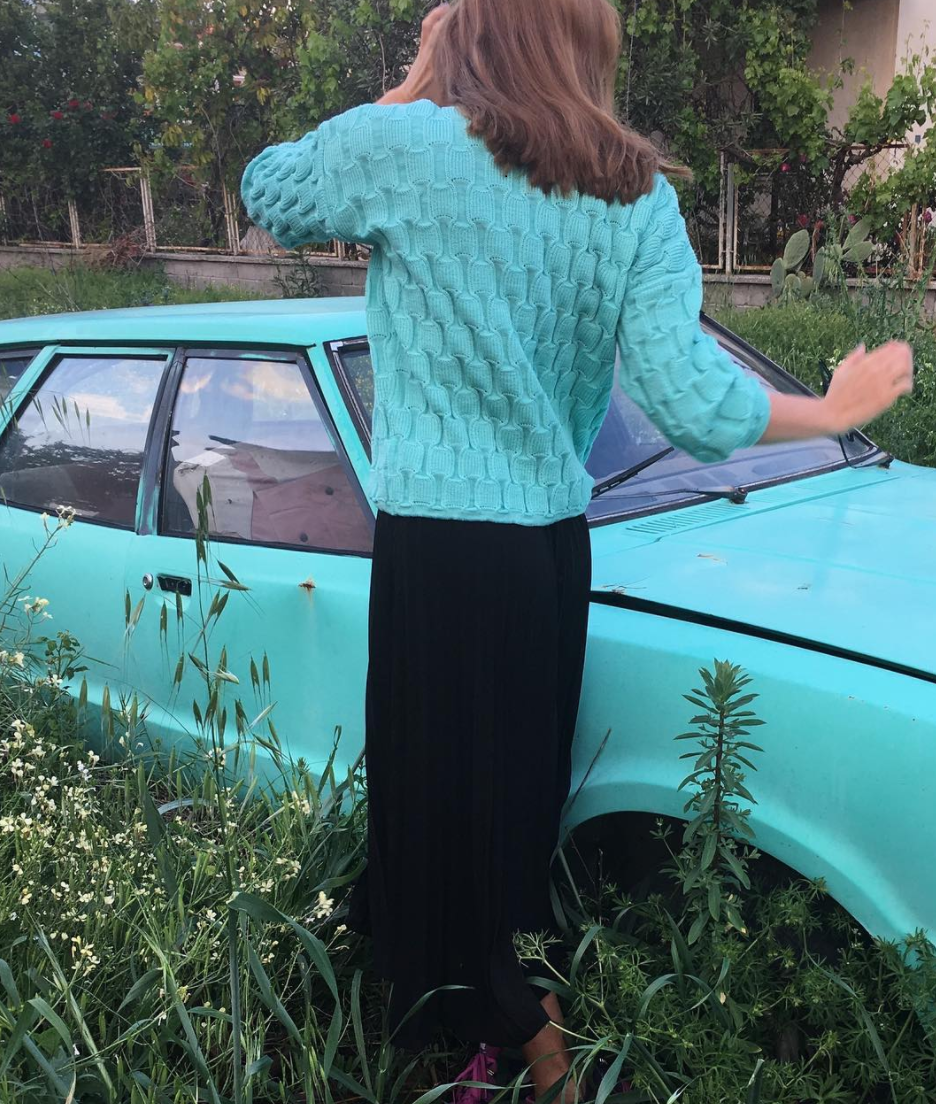 A woman in mint sweater in front of a car