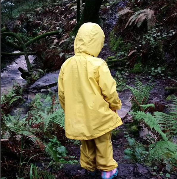 A kid with yellow raincoat standing in the forest