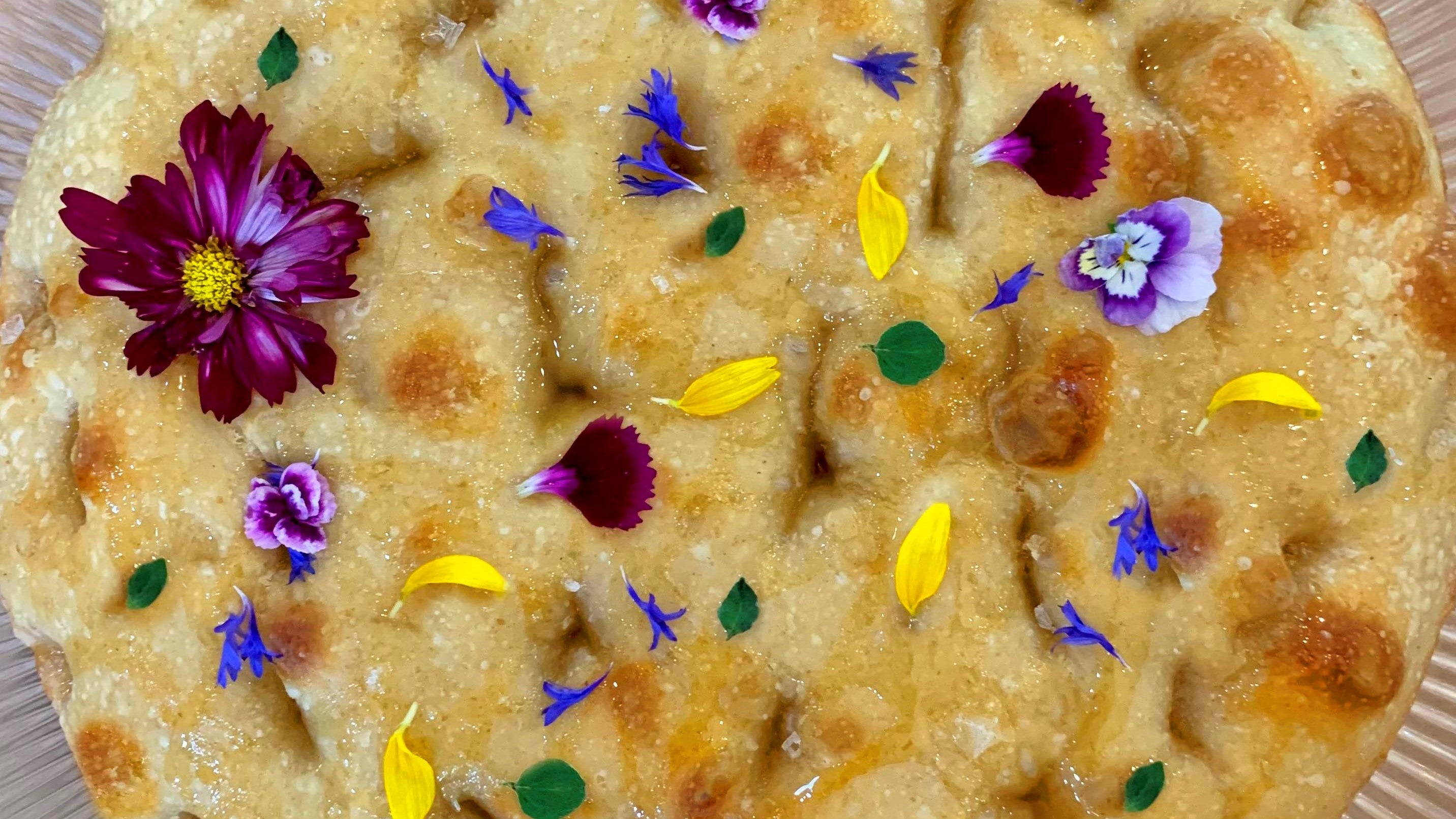 Round loaf of honey sea salt focaccia covered in edible flowers