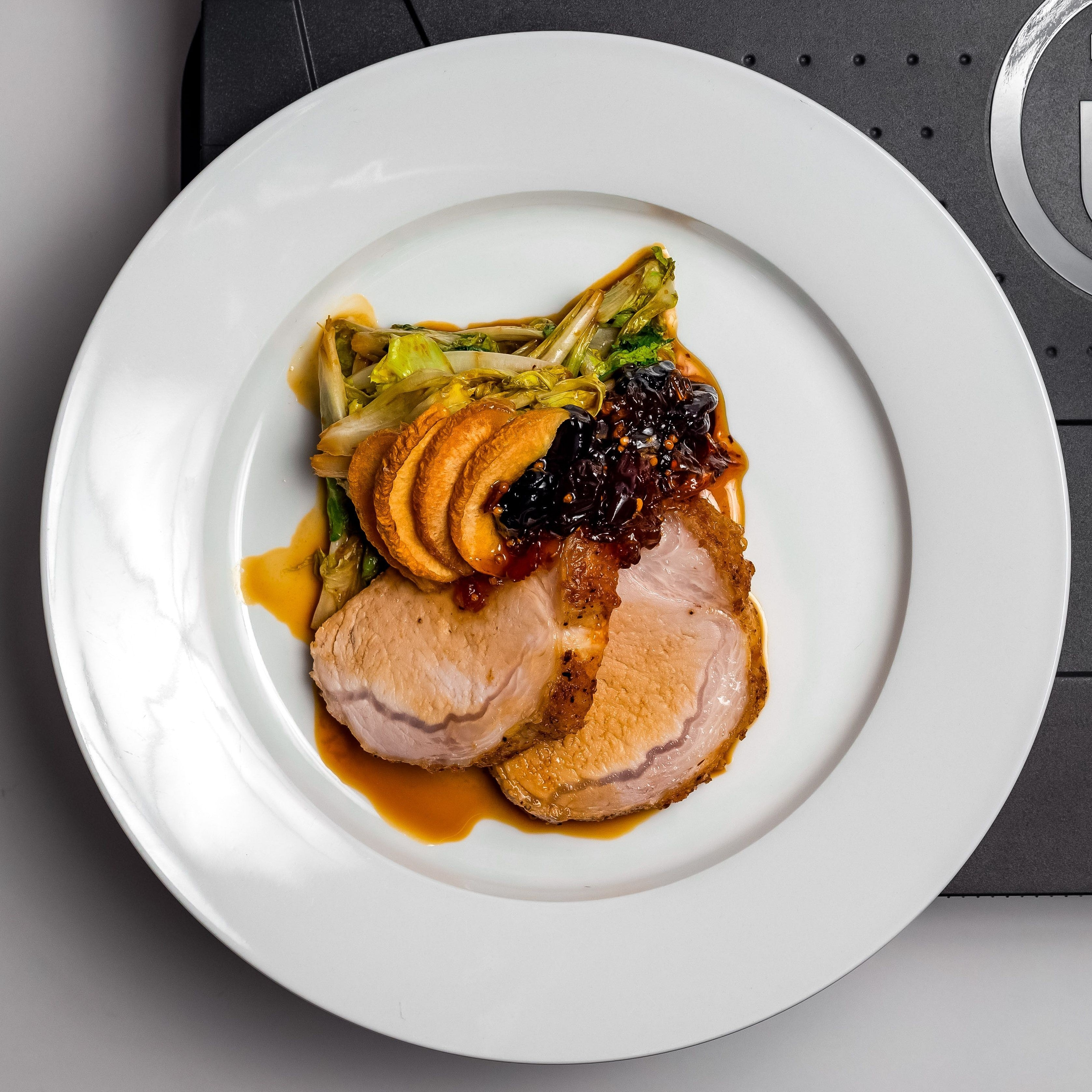 Sliced pork loin plated with quince chips, grape chutney, and frisee