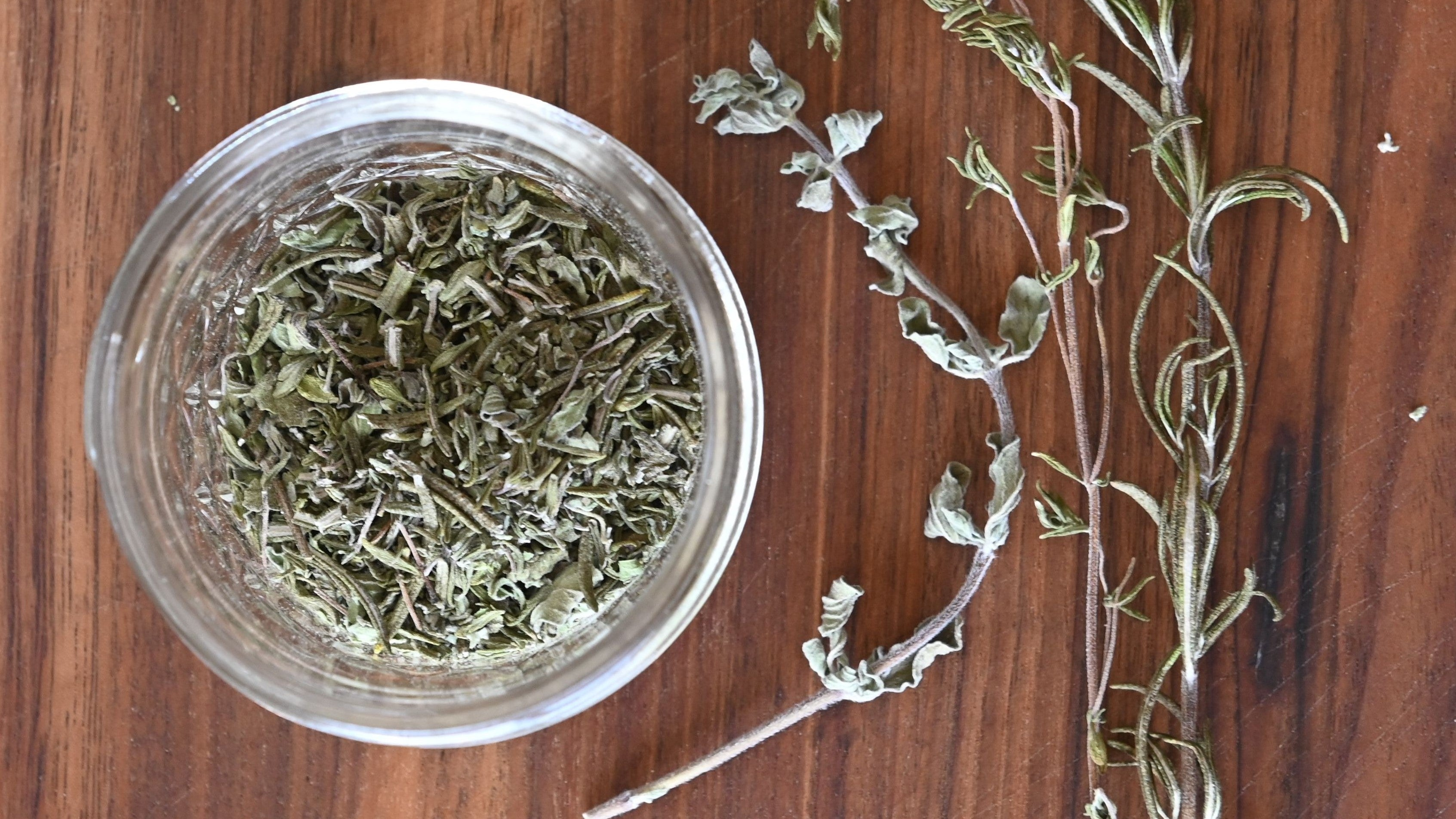 Jar of Italian herb blend next to dehydrated oregano, rosemary, and thyme