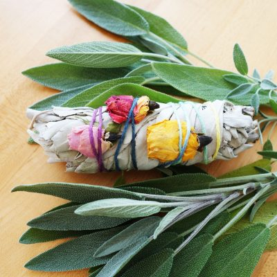 Tied sage and flower smudge surrounded by fresh sage leaves