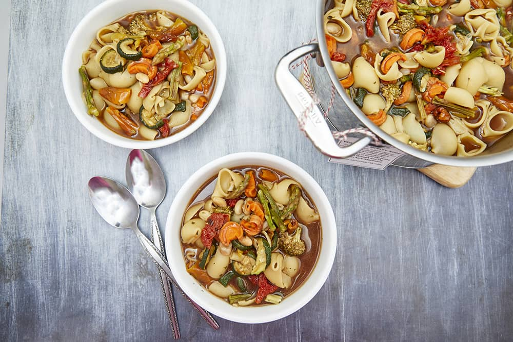 Two bowls and a metal pot of vegetable medley soup