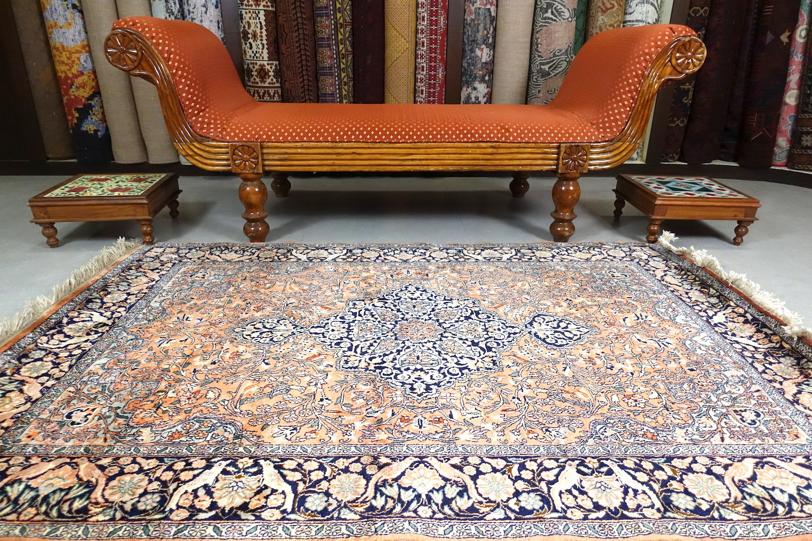 A 4 feet by 6 feet kashmiri silk on cotton rug. The colours used on the carpet are pink,beige,blue and black.