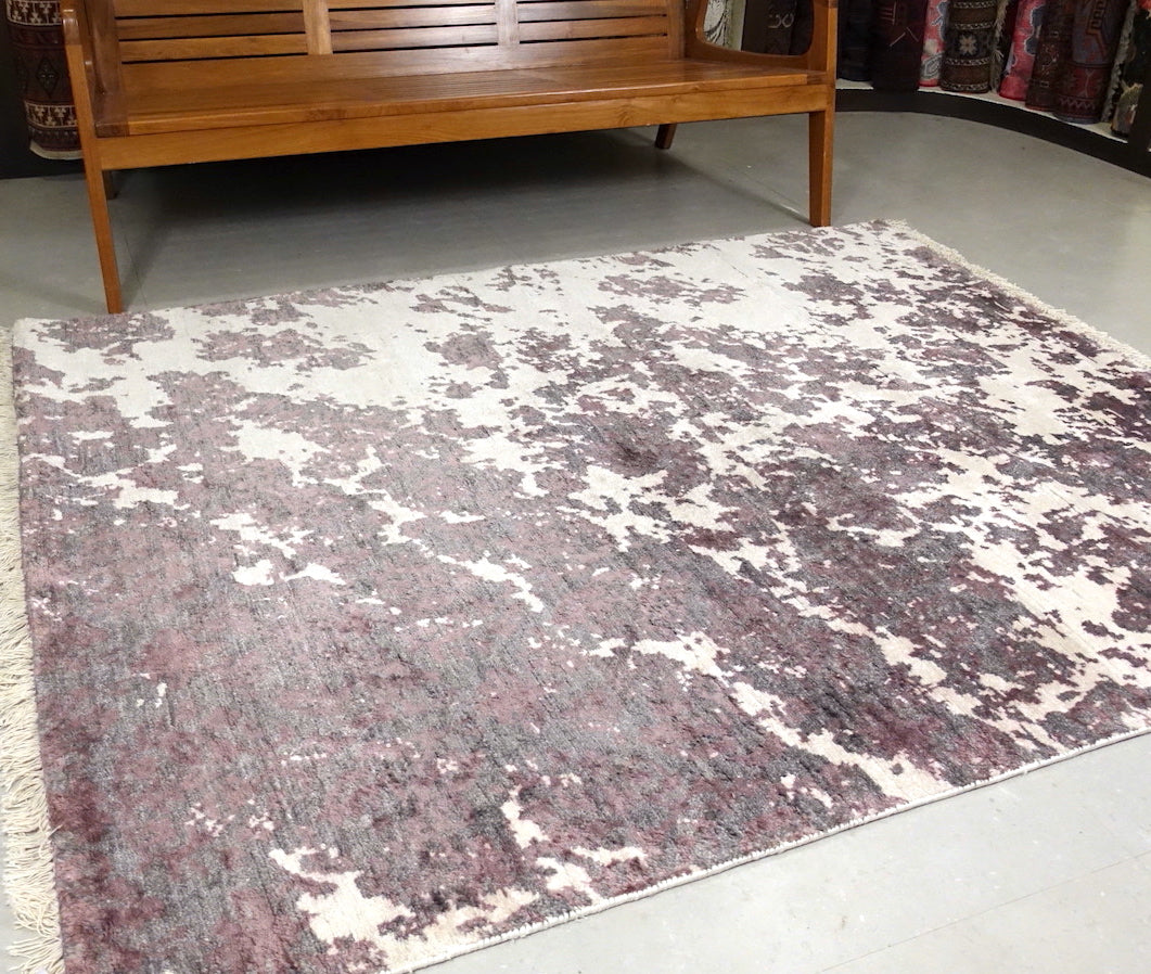 A 5 by 6 and half feet rug with an abstract design of light purple and white colours.