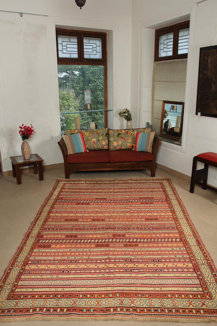 A 6.5 by 9.5 feet shirazi wool kilim. The colours mainly include orange, brick, brown, beige and tan.