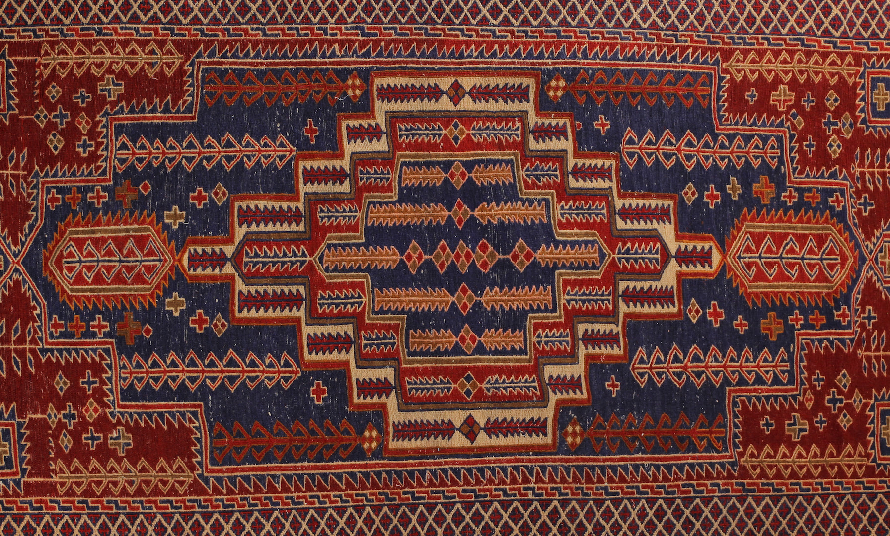 An almost 5 feet by 8 feet wool kilim, the colours include red,rust,beige and blue.