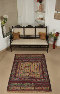 A 4 by 6 feet maliki wool kilim. The colours mainly include green, grey, tan, brick and pink.