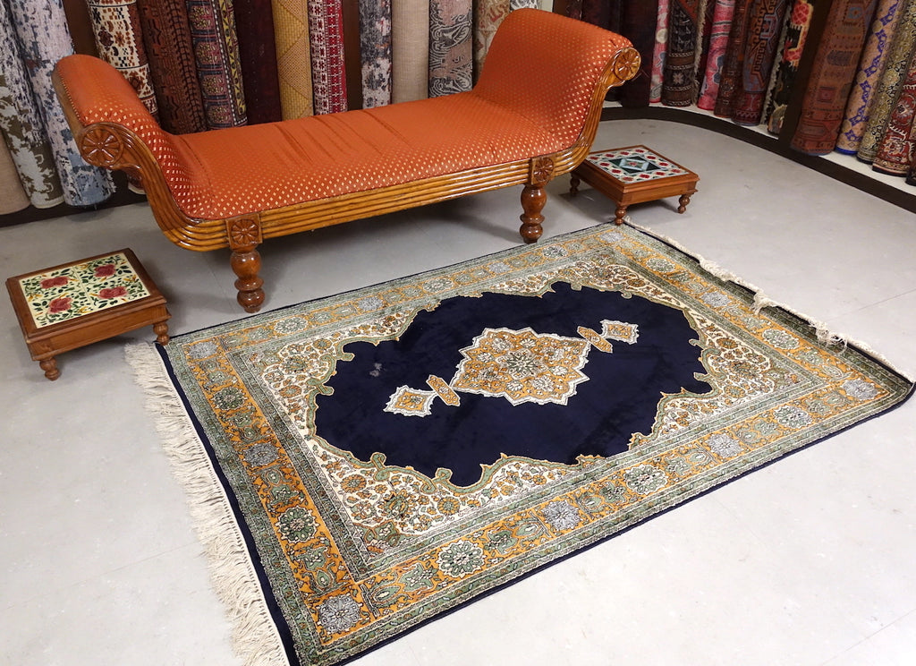 A 4 by 6 feet kashmiri silk on cotton rug. The colours used on the rug are beige,navy blue and yellow.