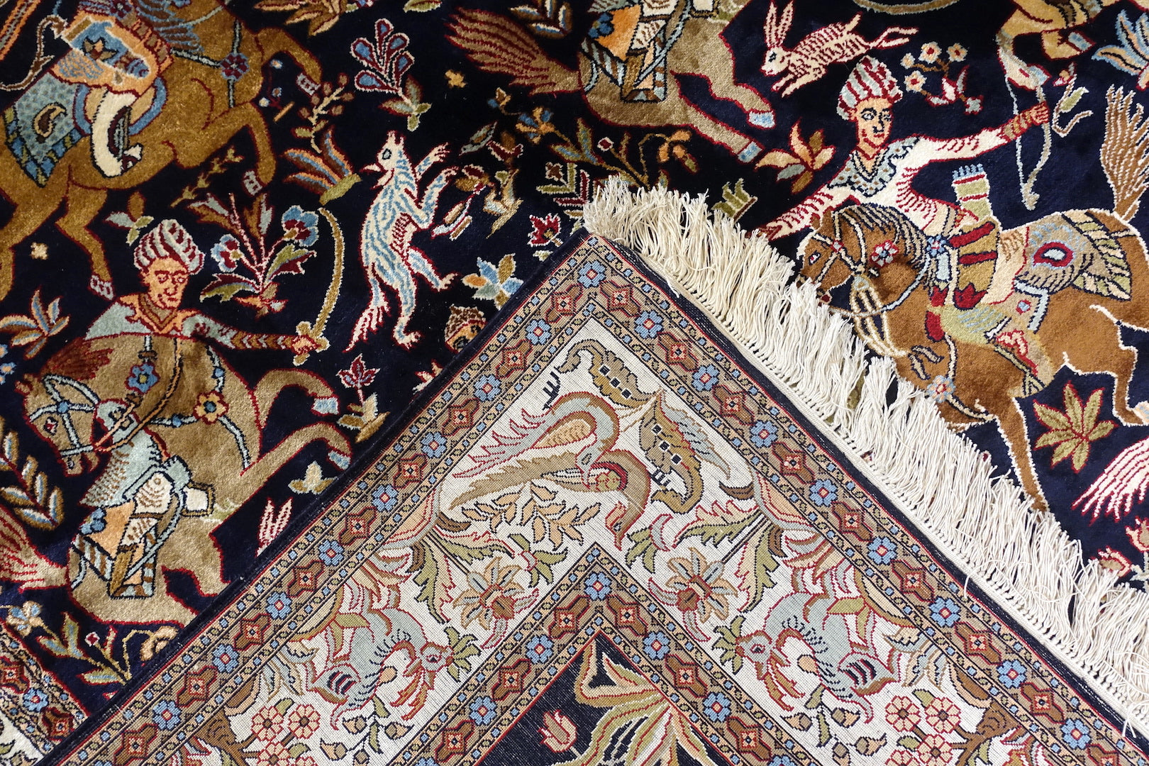 A 6 feet by 4 feet silk on silk rug from kashmir. The colours used in the rug are navy blue,beige,white,red,orange and yellow.