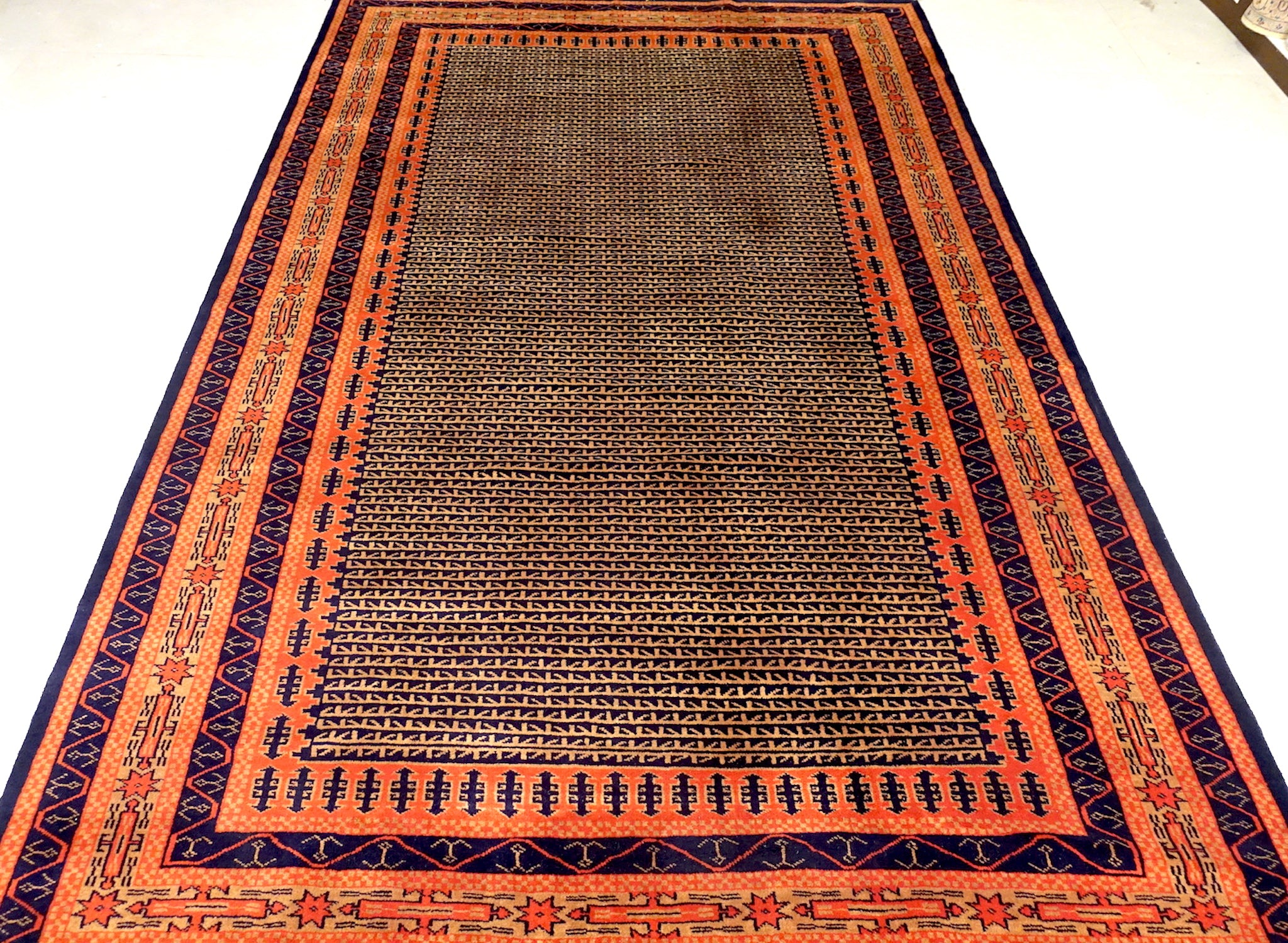 A 6 feet by 9 feet indian wool rug, the colours used on the rug are rust,brown,orange and dark blue.