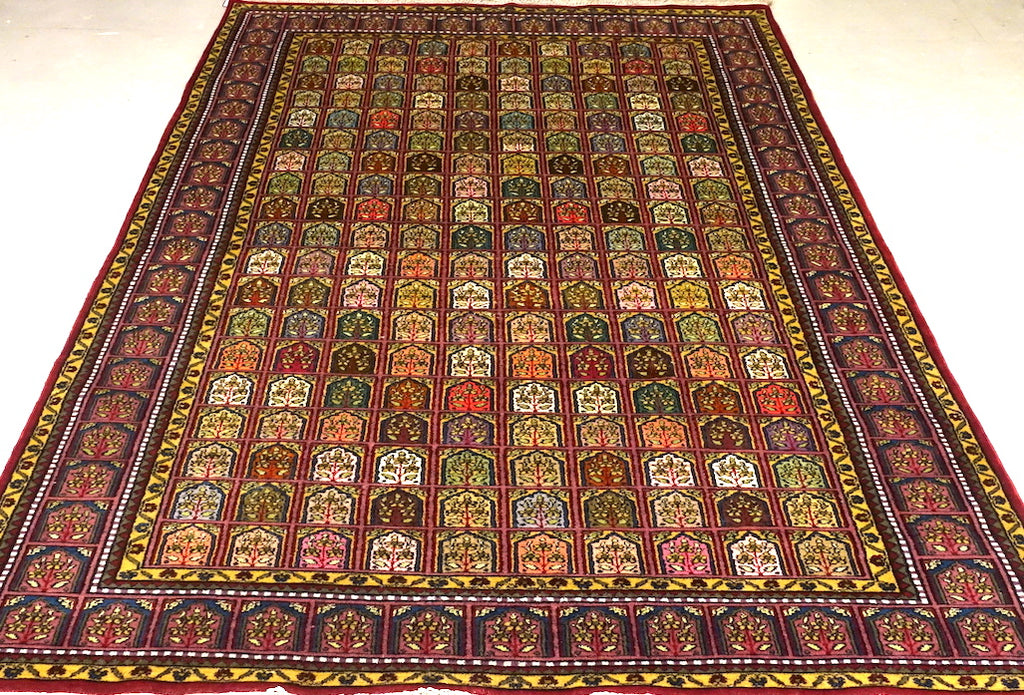 A 6 feet by 9 feet Kashmiri woolen rug, the colours used on the rug are red,orange,green, beige and blue.