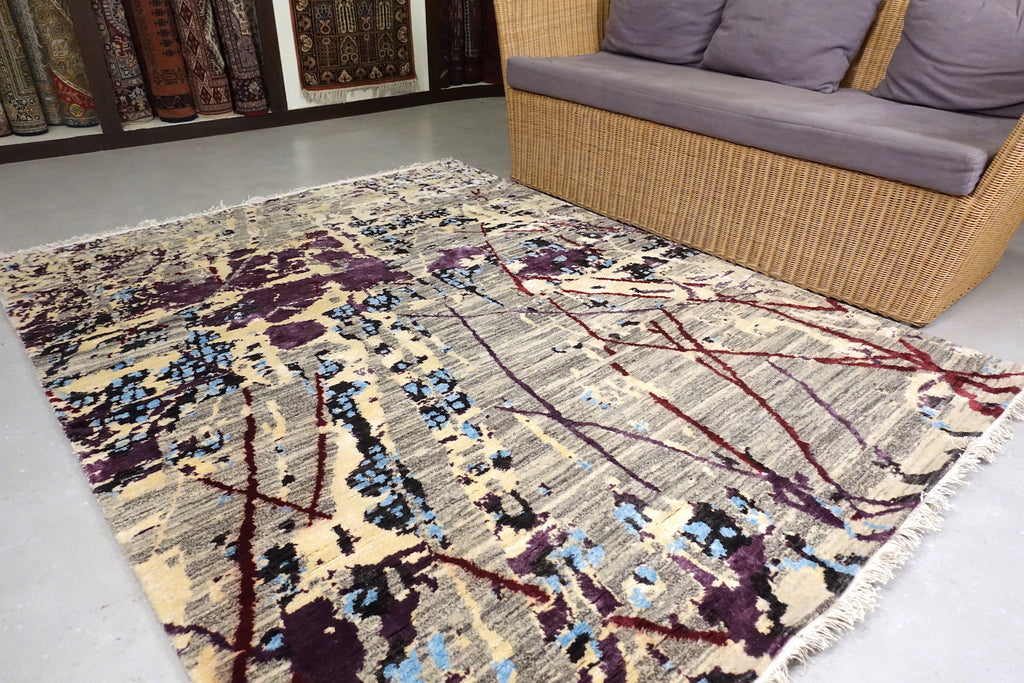 The rug/carpet consists of modern design. With a striped black and white based. Purple and Blue sprawled across like ink spread on paper. The rug is 5 feet by 7 feet.