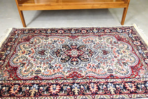 The rug measures 4 feet by 6 feet and is wool rug from central India. The colours used on the rug are beige,camel,blue and red.