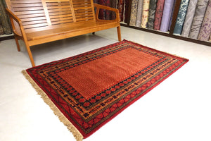 A 4 feet by 6 feet indian wool rug, the colours used on the rug are rust,brown,orange and dark blue.