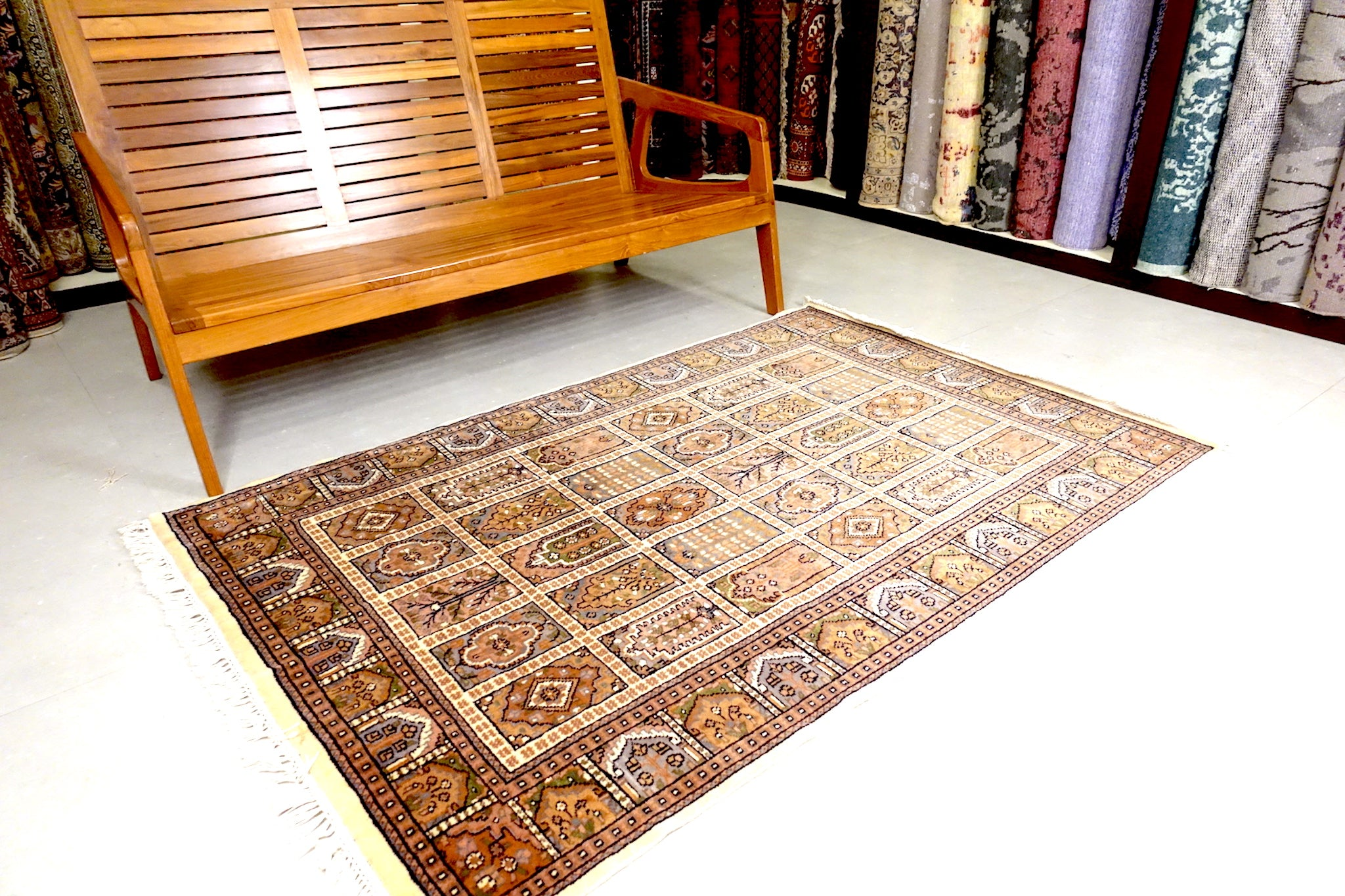 It is a 4 feet by 6 feet Indian wool rug. The colours used on the rug are beige,green and brown.