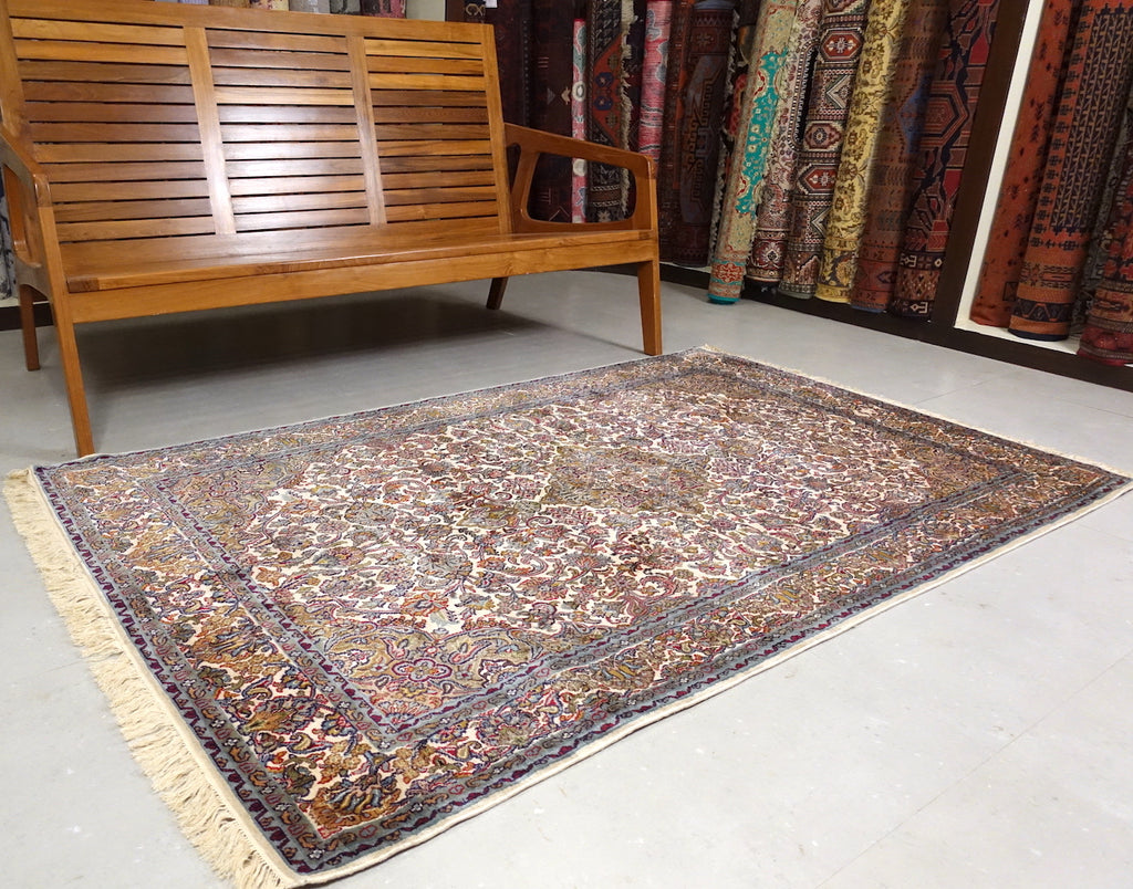 4 feet by 6 feet kashmiri silk on cotton rug, the colours used on the rug are beige,green,brown and blue.