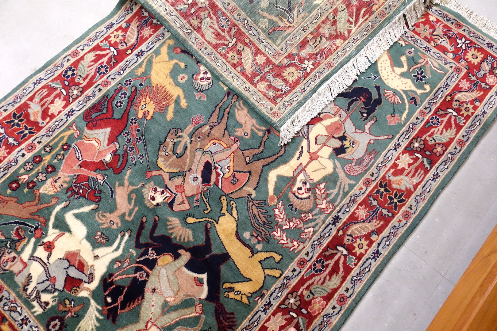 It is a 4 feet by 6 feet persian wool rug. It depicts a hunting scene and the colours used are gree,beige,red and black.