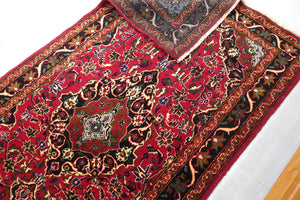 A 3.5 feet by 6 feet Afghan wool carpet, the colours used on the rug are pink, black, green, beige and brown.