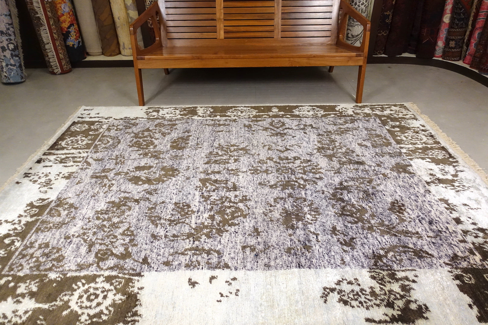 An almost 6 feet by 8 feet rug with an erased design based on the art nouveau style. The colour are dark green on a light creamish blue base.