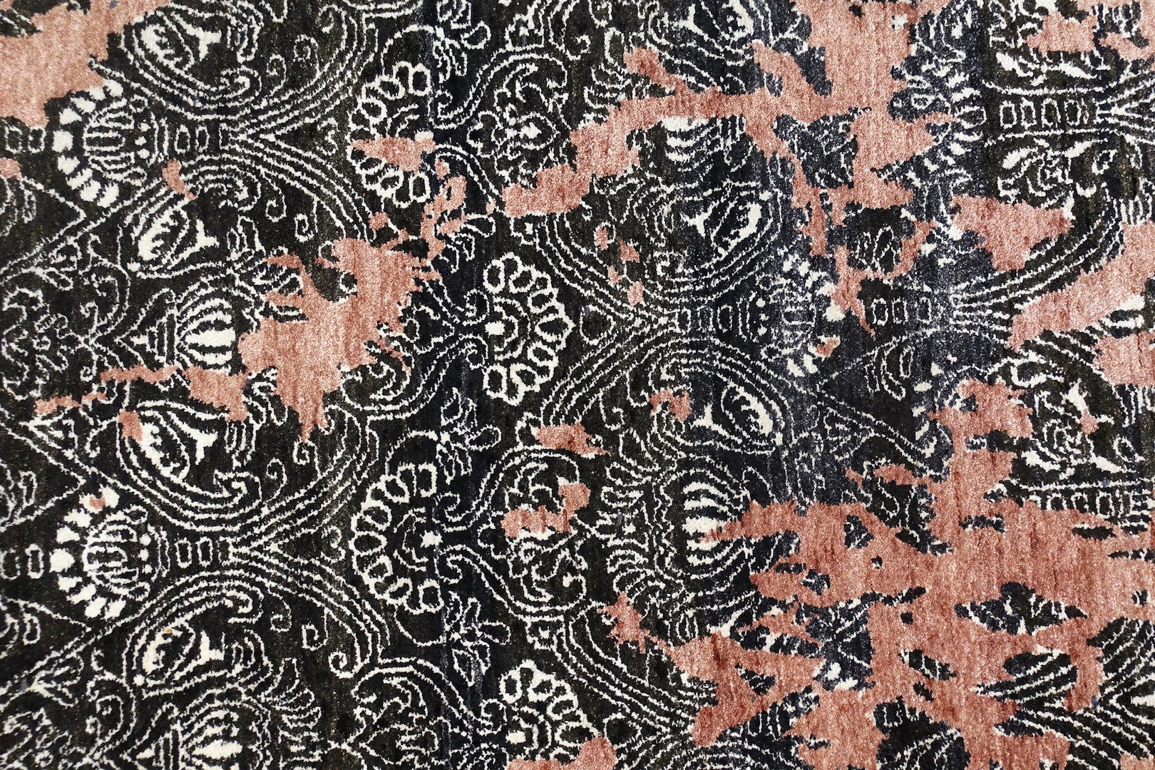 A 6 feet by 9 feet rug in pastel pink with black and white design elements.