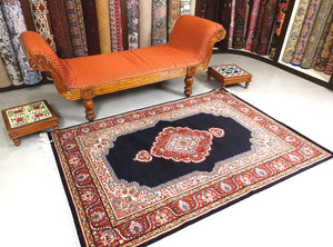 A 4 feet by 6 feet central Indian wool rug. The colours used are dark blue, beige,cream,red and brown.
