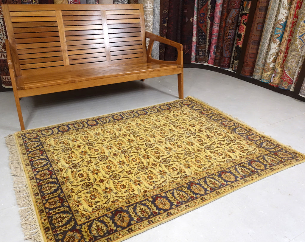 It is a 4 feet by 6 feet Indian wool rug with yellow, dark blue, rust and cherry colours.