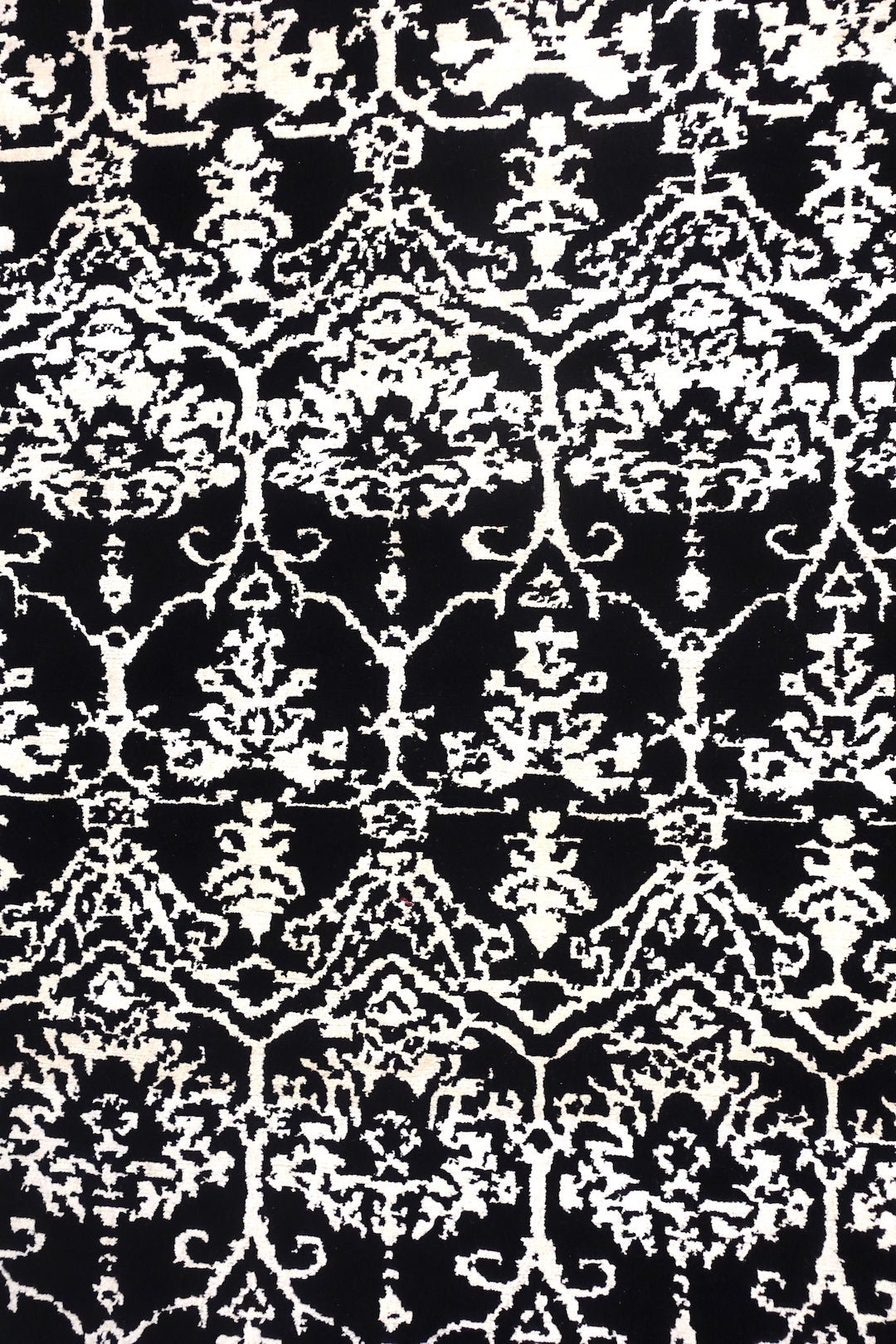 A 4 by 6 feet rug in black and white floral pattern.